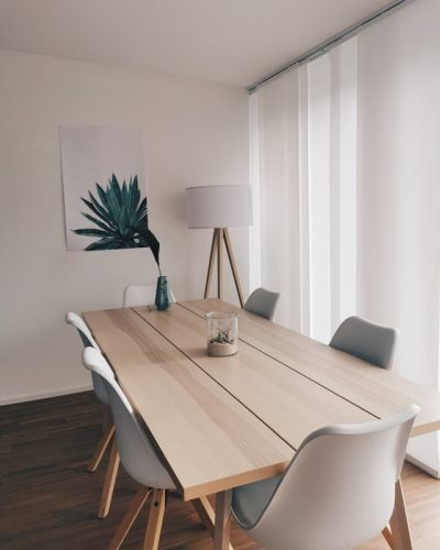 White dining room with soft coloured dining table and white curtains
