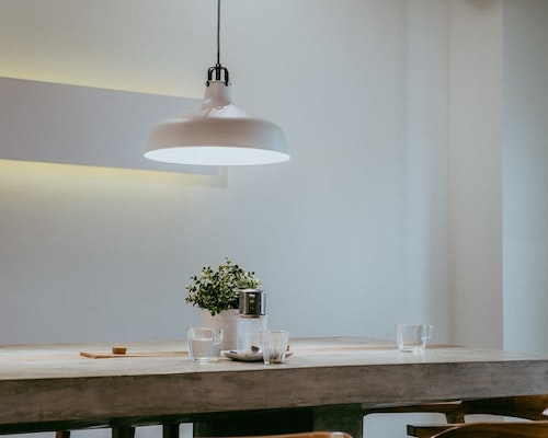 Low hanging ceiling light over a dining table