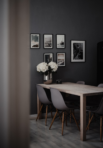 Dark grey dining room with monochrome artwork and light grey chairs